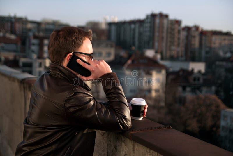 O homem de negócios está usando o callphone no telhado e no café bebendo imagem de stock royalty free