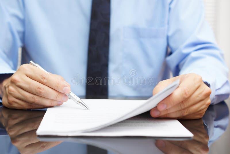 O homem de negócios está verificando o preço final no contrato foto de stock