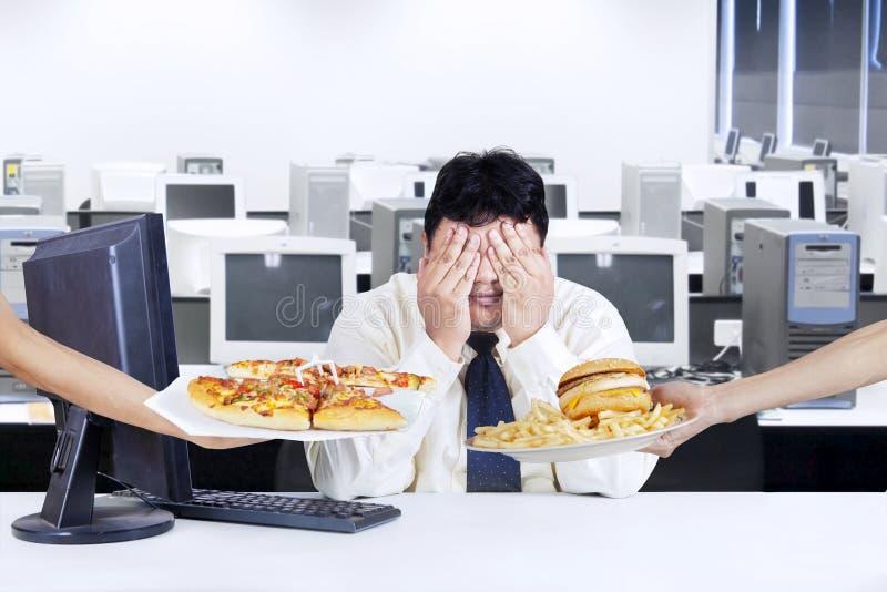 O homem de negócios evita a comida lixo fotografia de stock