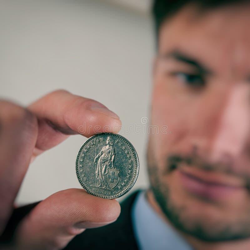 O homem de negócios examina uma moeda suíça com cinco francos imagem de stock royalty free