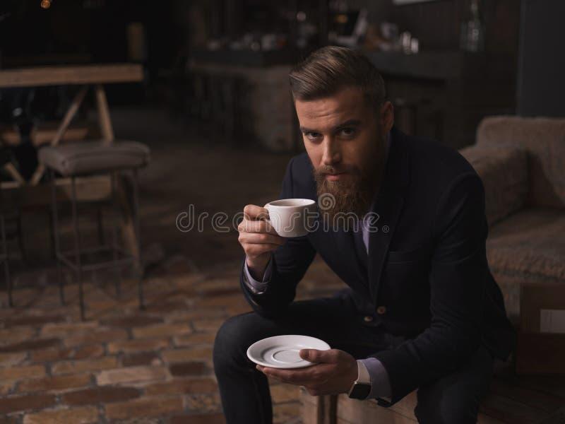 O homem de negócios farpado atrativo está apreciando o café quente foto de stock royalty free