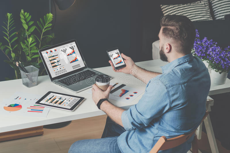 O homem de negócios farpado novo está sentando-se no escritório na tabela e está usando-se o portátil com cartas, gráficos e diag foto de stock royalty free
