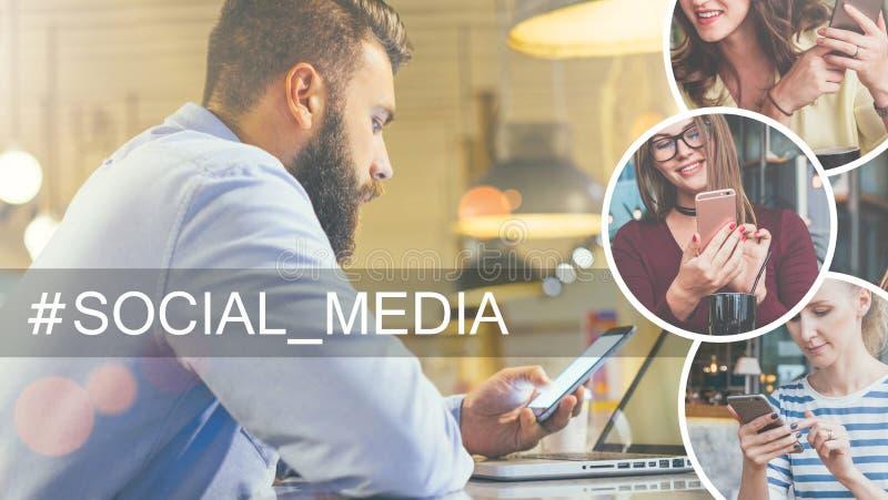 O homem de negócios farpado novo na camisa azul senta-se na tabela no café e no smartphone do uso, portátil na frente dele fotos de stock