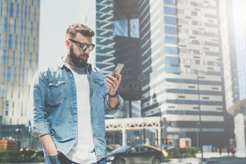 O homem de negócios farpado novo nos óculos de sol está na rua da cidade e usa o smartphone Homem que olha na tela do telefone fotografia de stock royalty free