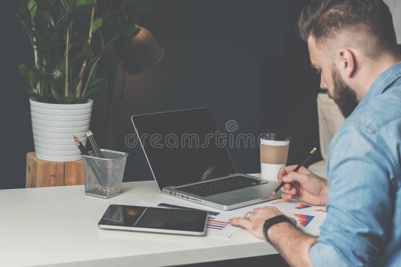 O homem de negócios farpado novo senta-se no escritório na tabela, usando a tabuleta digital e explora-se as cartas, fazendo anot foto de stock