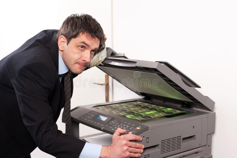 O homem de negócios faz o dinheiro falso na máquina da cópia fotos de stock royalty free