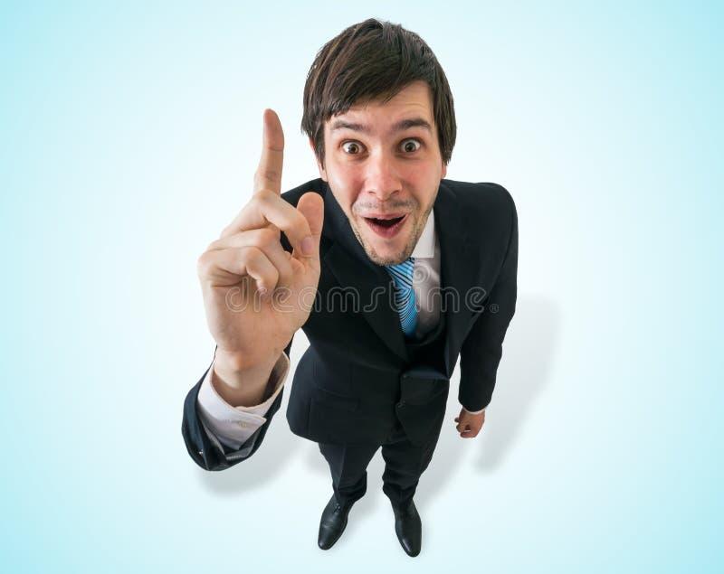 O homem de negócios feliz novo tem uma ideia e mantém o dedo imagem de stock royalty free
