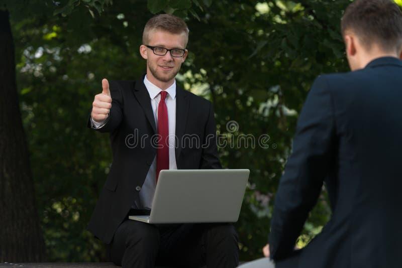 O homem de negócios feliz que mostra os polegares levanta o sinal fotografia de stock royalty free