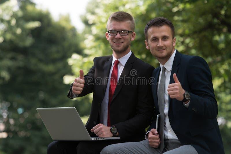 O homem de negócios feliz que mostra os polegares levanta o sinal imagem de stock royalty free