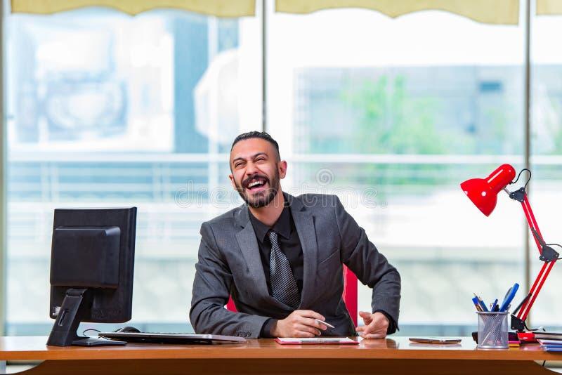 O homem de negócios feliz que senta-se na mesa foto de stock royalty free