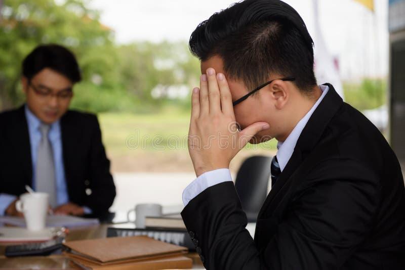 O homem de negócios forçado da dor de cabeça senta-se perto do gerente fotos de stock