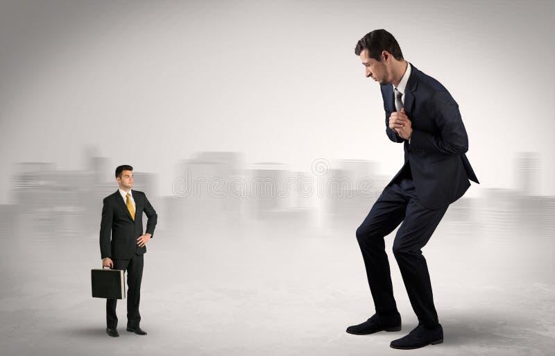 O homem de negócios gigante está receoso do executor pequeno foto de stock