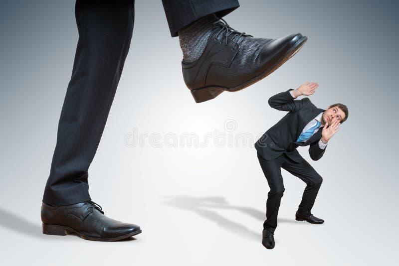 O homem de negócios grande irritado está abusando o empregado pequeno foto de stock