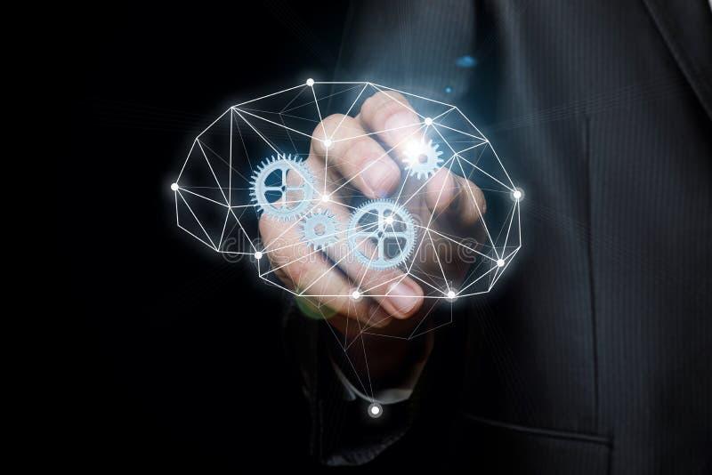 O homem de negócios introduz a engrenagem no mecanismo do pensamento foto de stock