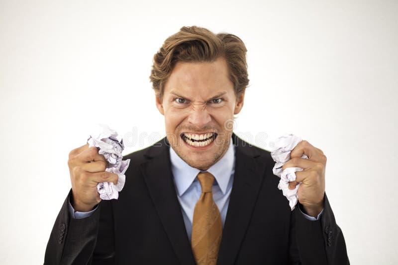 O homem de negócios irritado desintegra o papel fotografia de stock