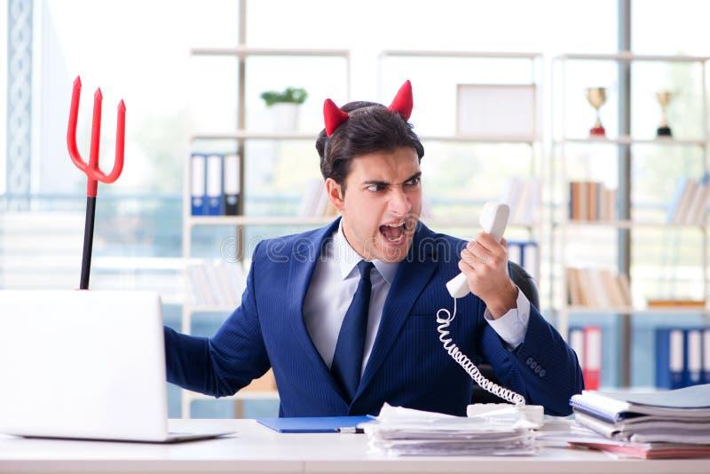 O homem de negócios irritado do diabo no escritório imagens de stock