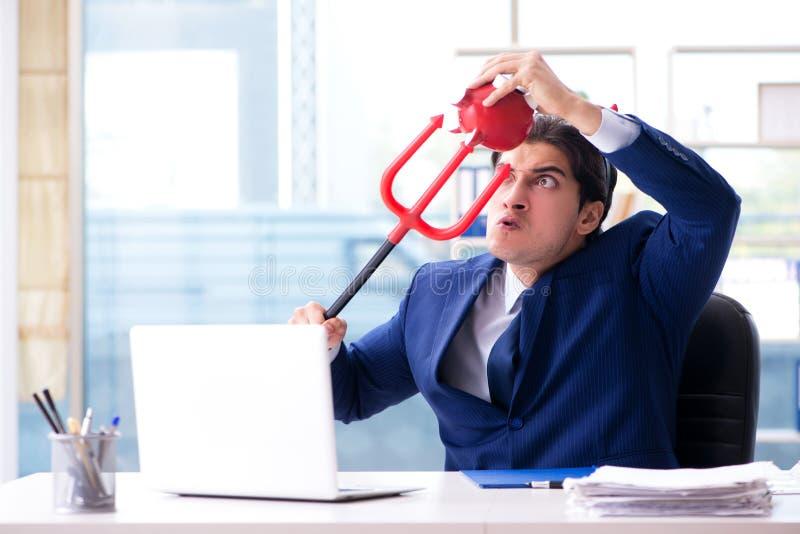 O homem de negócios irritado do diabo no escritório fotografia de stock royalty free