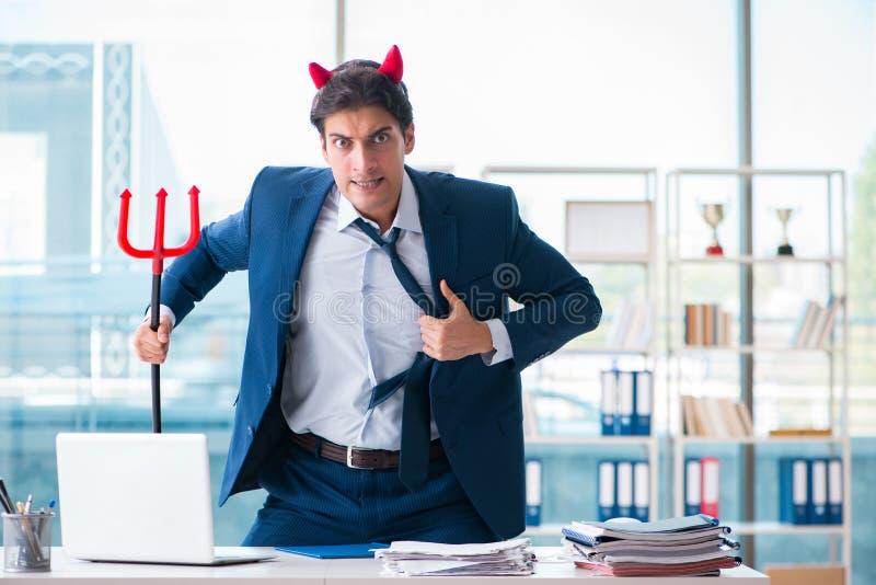 O homem de negócios irritado do diabo no escritório imagem de stock