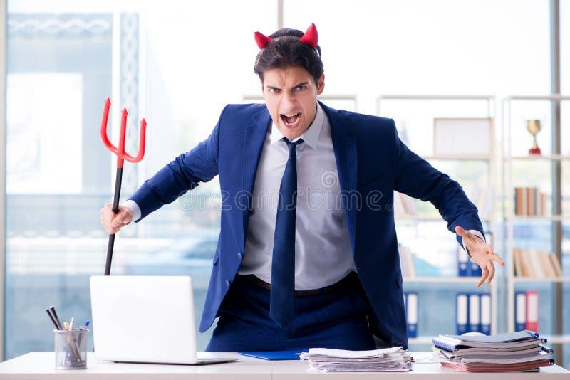 O homem de negócios irritado do diabo no escritório foto de stock