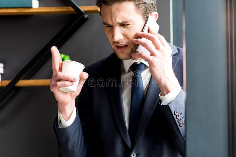 O homem de negócios irritado está falando no smartphone com cólera fotos de stock royalty free