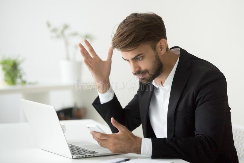 O homem de negócios irritado irritado forçou sobre o problema do smartphone em w foto de stock