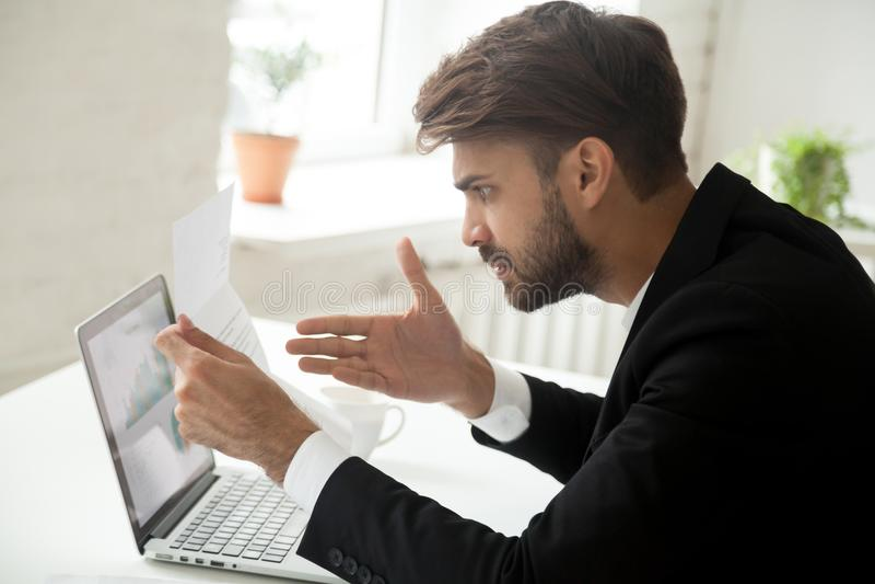 O homem de negócios irritado que sente indignante discorda com a informação dentro imagens de stock