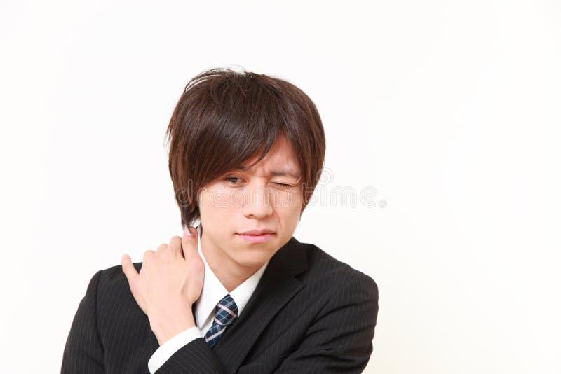 O homem de negócios japonês novo sofre da dor do pescoço imagem de stock