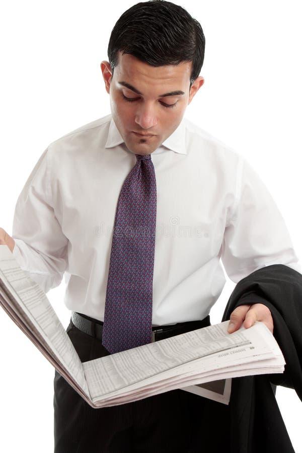 O homem de negócios lê preços de parte no jornal imagem de stock