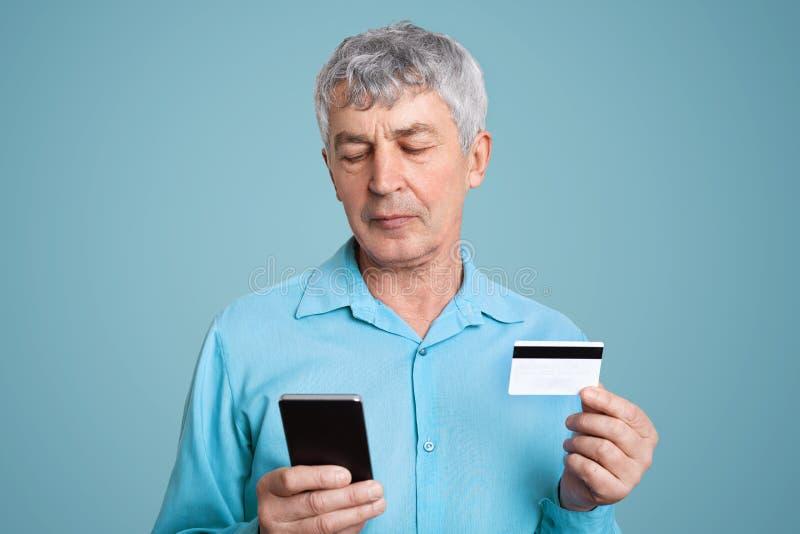 O homem de negócios maduro bem sucedido enrugado na roupa formal guarda o cartão moderno do telefone celular e do plástico, verif imagens de stock royalty free