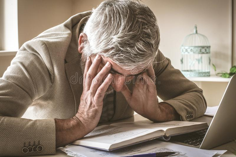 O homem de negócios maduro em seu escritório tem a dor de cabeça imagem de stock royalty free