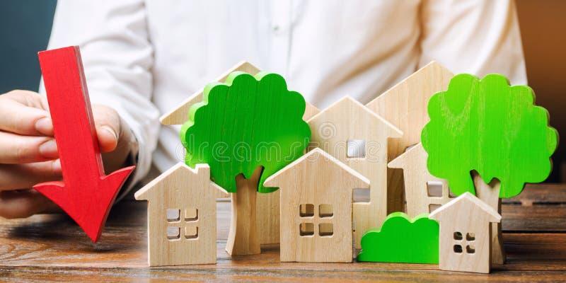 O homem de negócios mantém a seta perto das casas e das árvores de madeira O conceito de reduzir o investimento na construção de  imagens de stock