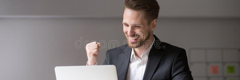 O homem de negócios milenar da foto horizontal sente a boa notícia recebida feliz em linha fotografia de stock royalty free
