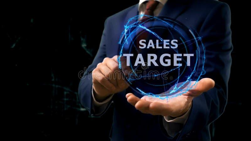 O homem de negócios mostra o alvo de vendas do holograma do conceito em sua mão imagens de stock royalty free
