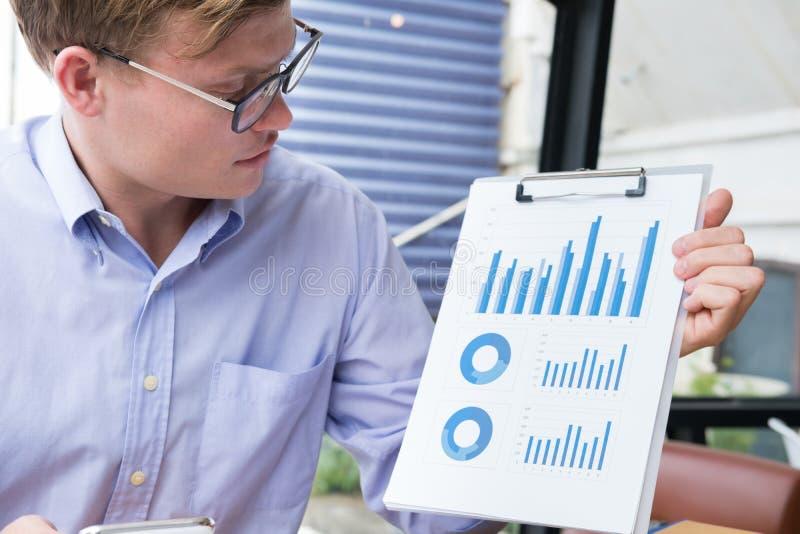 O homem de negócios mostra o diagrama financeiro do gráfico no escritório homem novo p fotografia de stock