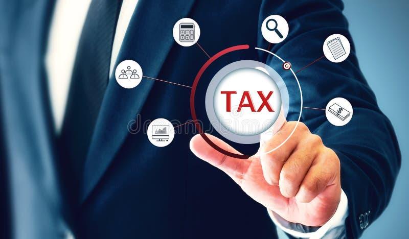 O homem de negócios mostrado em cartas e em dados, toca em um ícone que represente o conceito de pagar impostos fotos de stock royalty free