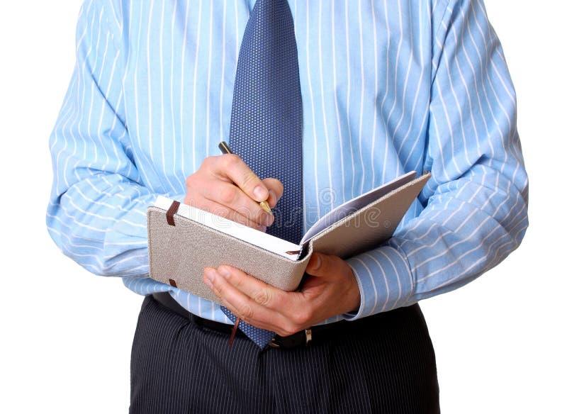 O homem de negócios na camisa azul com caderno e pena escreve fotografia de stock