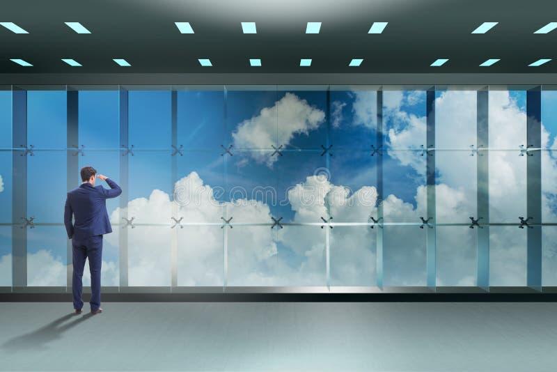O homem de negócios na frente da janela do escritório que pensa de desafios novos imagens de stock