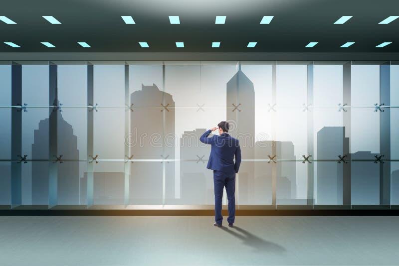 O homem de negócios na frente da janela do escritório que pensa de desafios novos imagens de stock royalty free