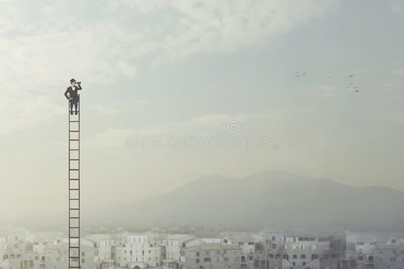 O homem de negócios na parte superior de uma escada longa observa a cidade com seus binóculos fotos de stock