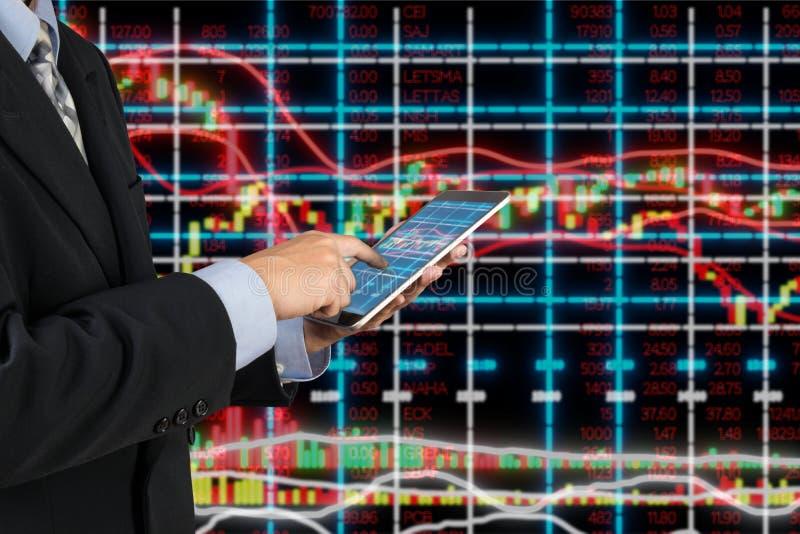 O homem de negócios na tabuleta sem fio de Digitas do uso do terno analisa o investimento na bolsa fotografia de stock royalty free