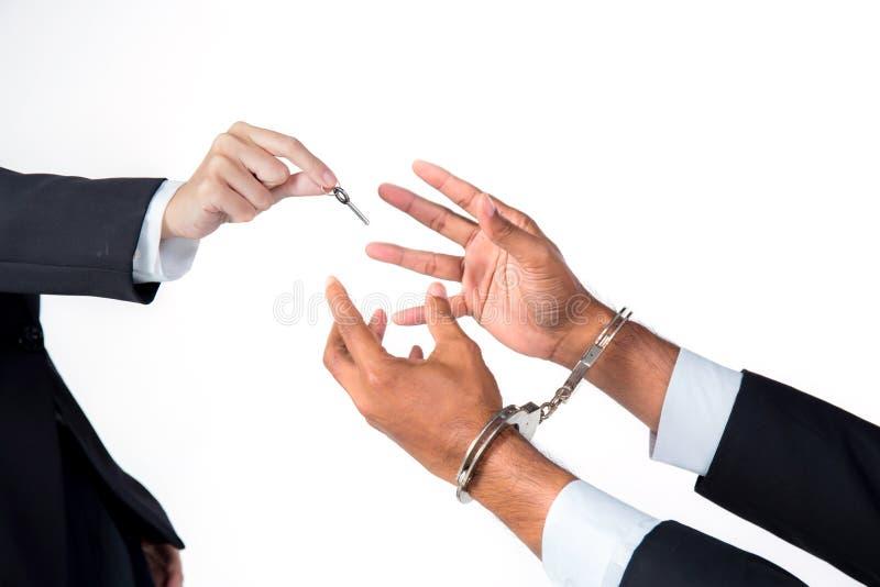 o homem de negócios nas algemas e a mulher entregam a resolução de oferecimento da chave fotos de stock