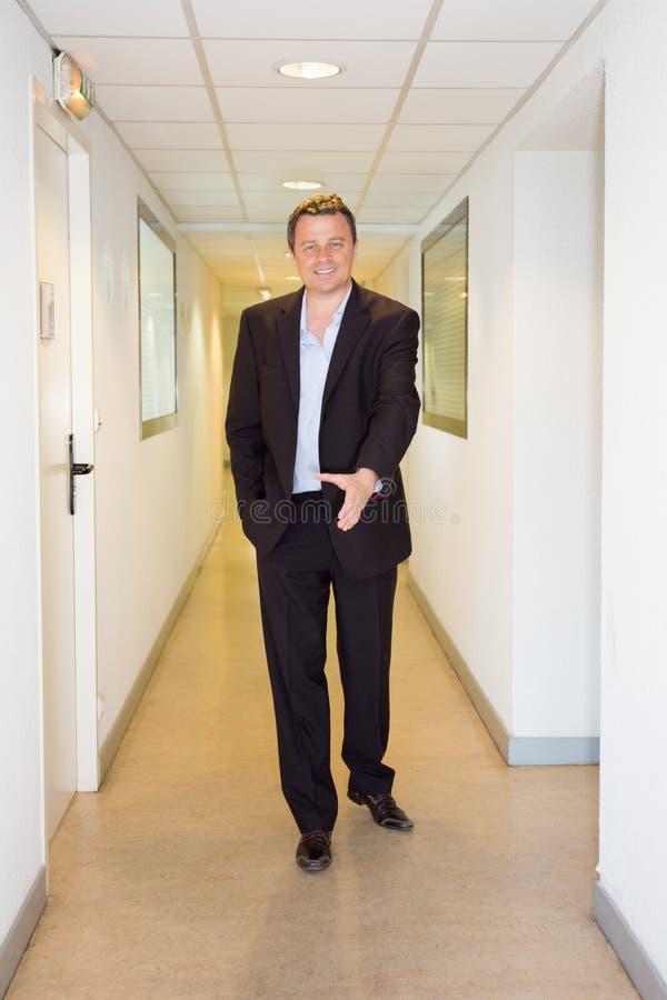o homem de negócios no corredor da empresa está preparando-se para cumprimentar uma pessoa que chega pela nomeação fotografia de stock royalty free