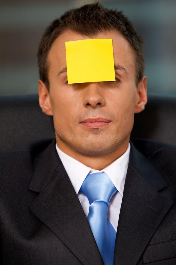 O homem de negócios no escritório com nota adesiva vazia colou à testa imagens de stock