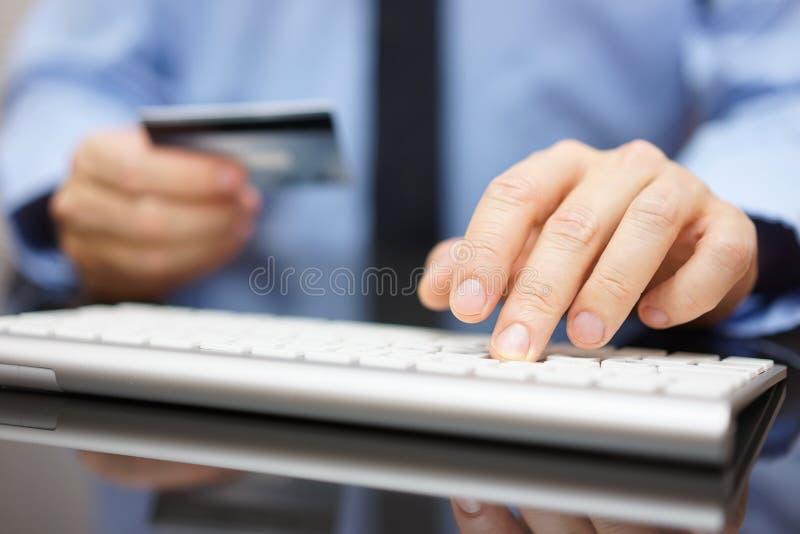 O homem de negócios no escritório está fazendo a transferência bancária ou na linha purchas fotografia de stock royalty free