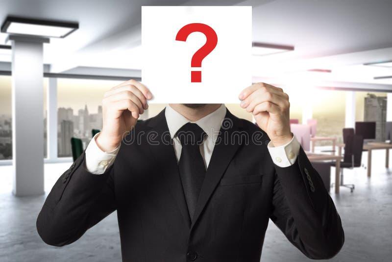 O homem de negócios no escritório moderno esconde a cara atrás da ilustração do ponto de interrogação 3D do sinal imagem de stock