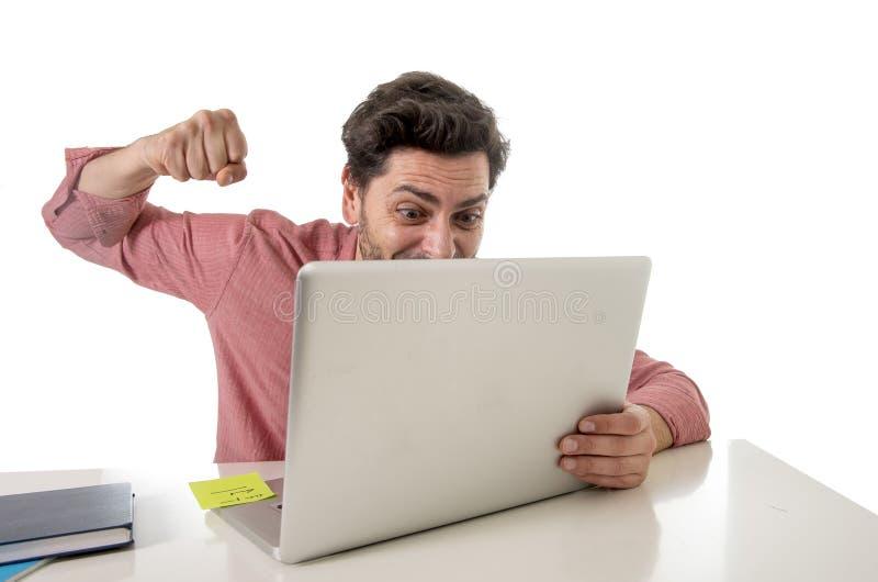 O homem de negócios no funcionamento do escritório forçado no portátil do computador sobrecarregou o perfurador de jogo no esforç imagens de stock