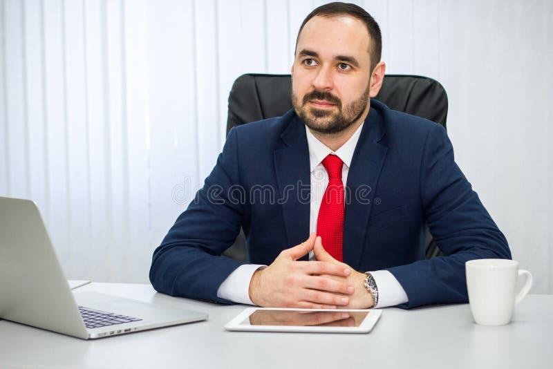 O homem de negócios no terno e no laço vermelho escuta com cuidado seu interl fotografia de stock