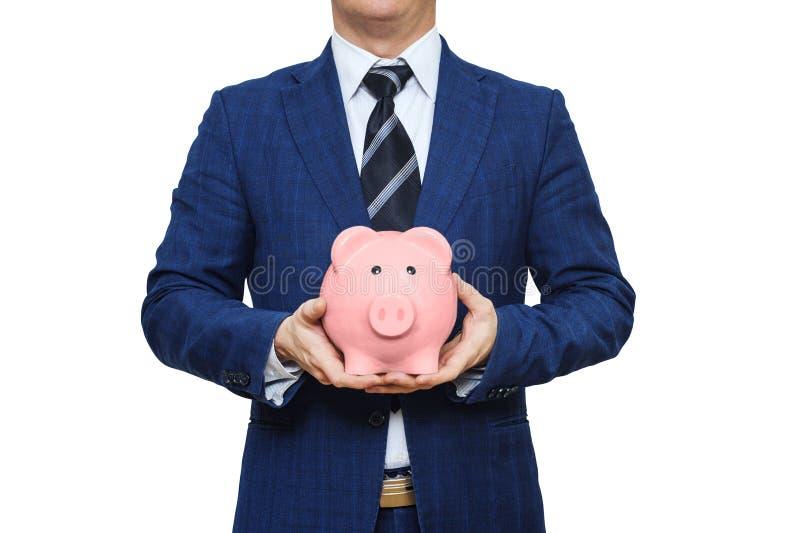 O homem de negócios no terno está guardando o mealheiro Caixa de dinheiro do porco da terra arrendada do homem de negócios Concei fotos de stock