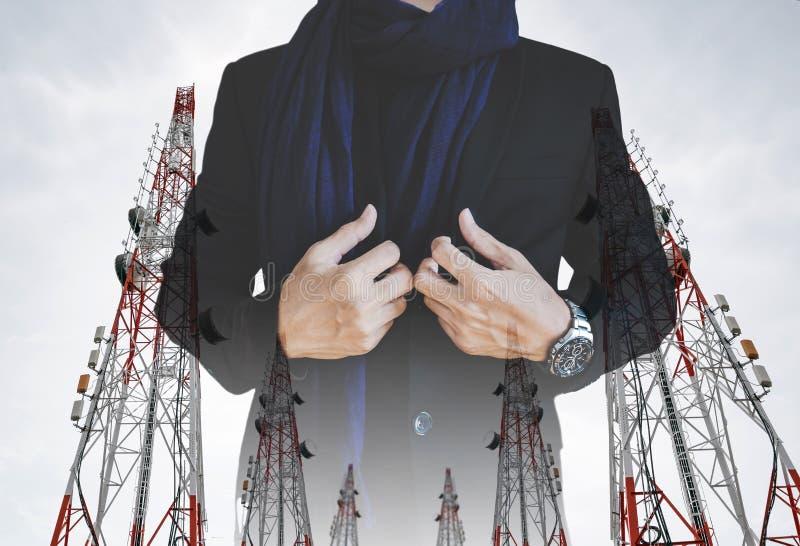 O homem de negócios no terno ocasional com telecomunicação da exposição múltipla eleva-se com antenas e antena parabólica da tevê foto de stock royalty free
