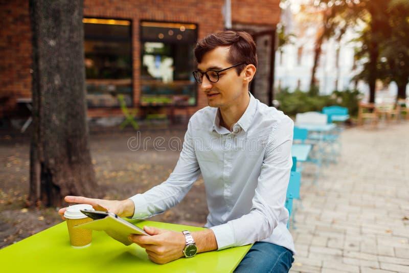 O homem de negócios novo aprecia o café no café exterior usando a tabuleta Chá bebendo do indivíduo considerável na rua da cidade fotografia de stock royalty free